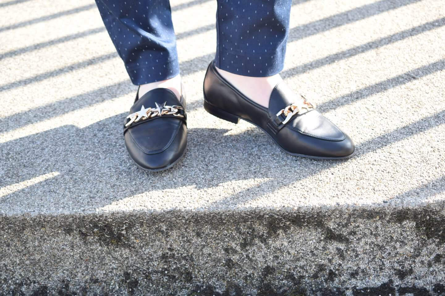A pair of black Faith Loafers with a metal star detail